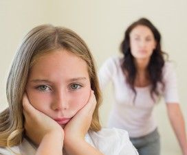 Sad girl with mother in background