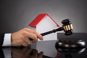 Close-up Of Judge With House Model Hitting Gavel At Desk